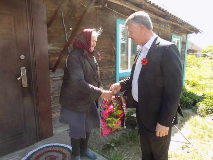 Сергій Фесик вручає подарунок ветеранці війни