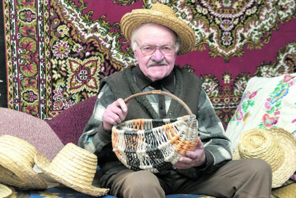 Дідусь Іван плете брилі із житньої соломи та кошелі